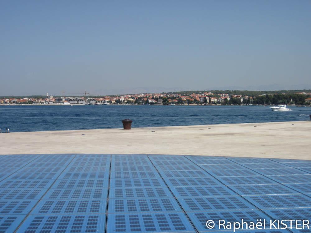 Front de mer - Le salut au Soleil (grand cercle composé de lampes de verre coloré alimentées par des cellules photovoltaïques)